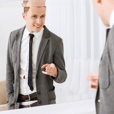 You are best. Smiling young man pointing on himself in mirror with help of his index fingers